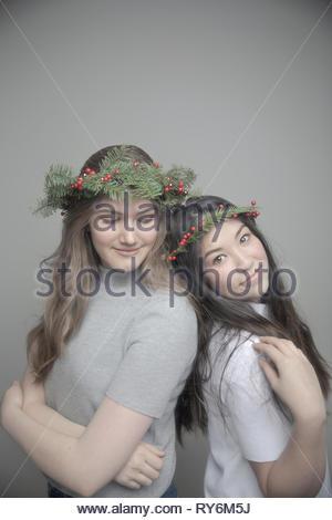 Ritratto fiducioso belle ragazze adolescenti che indossa il natale corone di fiori sulla testa Foto Stock