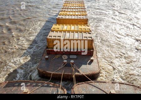 Chiatte piatta caricata con contenitori trainato a valle del fiume Tamigi, Londra, Regno Unito, Foto Stock