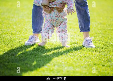 Vista ritagliata della madre del bambino di supporto figlia e di aiutarla a fare i primi passi. Mamma e figlia camminando sul prato verde nel parco d'estate. Foto Stock