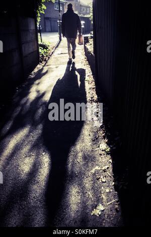 Uomo che cammina vicolo giù Foto Stock