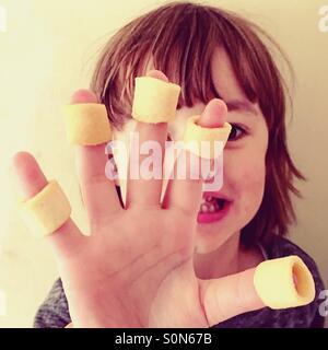 Piccolo 4 anno vecchio ragazzo con patatine sulle sue dita. Foto Stock