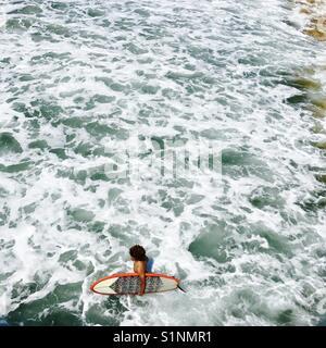 Un surfista maschio passeggiate fuori per il surf. Manhattan Beach, California USA. Foto Stock