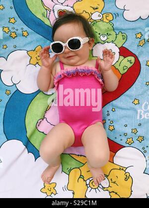 Un simpatico baby girl in rosa di un costume da bagno, indossando occhiali da sole e giacenti su una cura porta asciugamani. Foto Stock