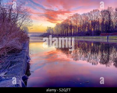 Colorati e drammatico all'alba o al tramonto su un inverno paesaggio forestale con un fiume che scorre attraverso di essa che riflette le nuvole colorate e cielo Foto Stock