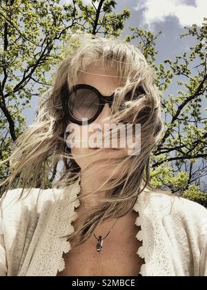 Donna sotto un albero in una giornata di vento. Foto Stock