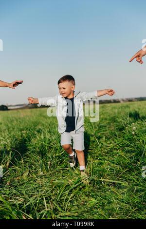 Little Boy desidera tenere le mani dei suoi genitori all'aperto. Foto Stock