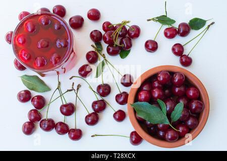 La ciliegia sulla tavola di legno, di ciliege acide e un bicchiere di freddo succhi di ciliegie. vista superiore Foto Stock