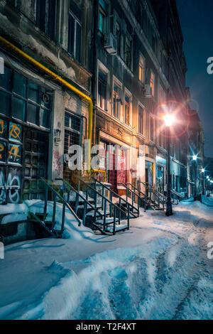 Bella e antica viuzza coperta di neve in inverno nel centro di Bucarest con vecchi edifici shot nella notte ben illuminati da lampade stradali Foto Stock