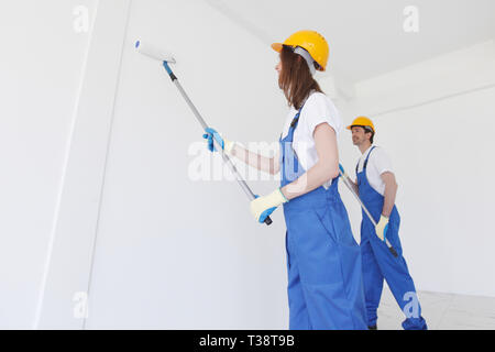 Due lavoratori della pittura la parete con rullo di vernice , vuoto lo spazio di copia Foto Stock