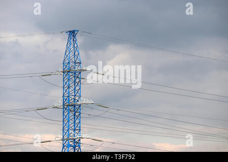 Linea elettrica ad alta tensione post con fili elettrici e condensatori su sfondo con cielo nuvoloso. Linea di trasporto di elettricità, alimentazione Foto Stock