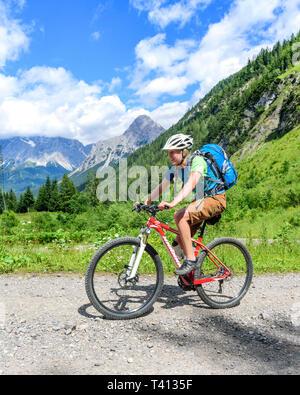 Giovane donna ascendere con mountainbike sulla strada di ghiaia Foto Stock
