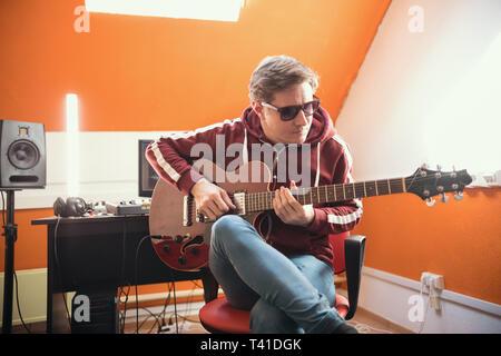 Un musicista uomo a suonare la chitarra in studio Foto Stock