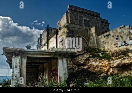 Un hotel abbandonato in rovine. Un hotel abbandonato nelle rovine di Mellieha, Malta impostato sul bordo di una collina. Foto Stock