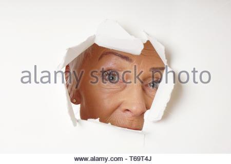 Vigile donna anziana guardando attraverso il foro Foto Stock