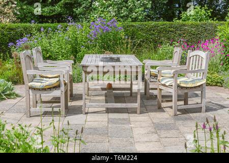 Tavolo in legno e sedie in un giardino ornamentale Foto Stock