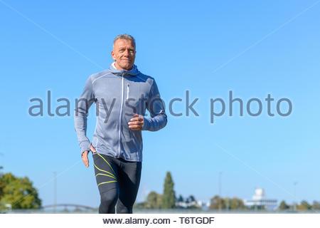 Grigio uomo sorridente in esecuzione attraverso un parco Foto Stock
