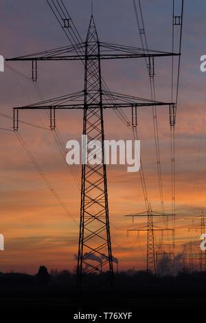 Silhouette di linee elettriche ad alta tensione e tralicci che portano ad un vapore stazione di alimentazione nella parte anteriore di un colorato dopo il cielo al tramonto. Karlsruhe, Germania Foto Stock