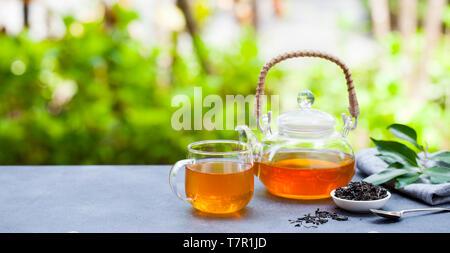 Il tè in tazza di vetro e teiera in estate sfondo all'aperto. Copia dello spazio. Foto Stock