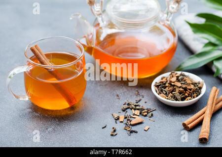 Il tè con la cannella in coppa di vetro e teiera in pietra grigia sullo sfondo. Foto Stock