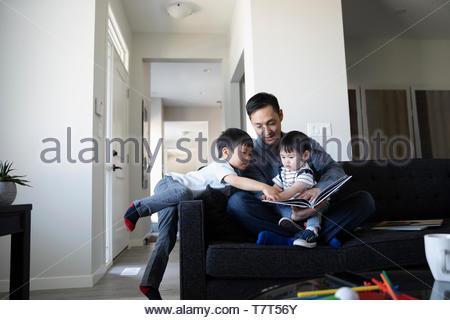 Padre e figli toddler leggendo un libro sul divano Foto Stock