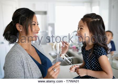 Felice, giocoso madre e figlia di cottura, le fruste a tenuta con la glassa Foto Stock