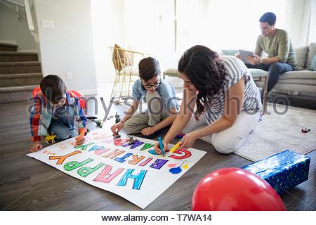 Famiglia compleanno di colorazione segno vivente sul pavimento della camera Foto Stock
