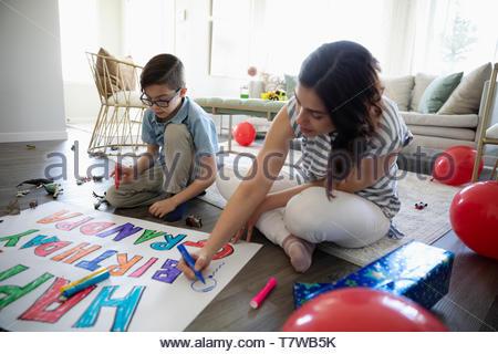 Fratello e Sorella di colorazione segno di compleanno sul pavimento Foto Stock