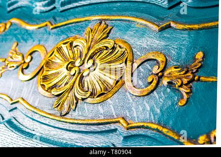 Dettagli floreali su una cassa di legno, in stile antico. Close up di sculture giallo su splendidamente scolpito arredamento blu sullo sfondo. Foto Stock