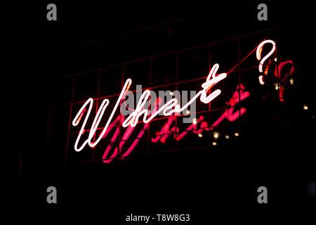 Domanda che cosa in neon rosso a colori su sfondo nero. Trendy 80s concetto. Foto Stock
