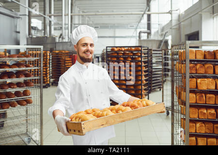 Sorridente baker in bianco uniforme con vassoi di pane fresco di costi nella produzione di panetteria. Foto Stock