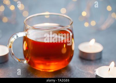 Tè nero in tazza di vetro con candele e ghirlanda luminosa. Sfondo grigio. Copia dello spazio. Foto Stock