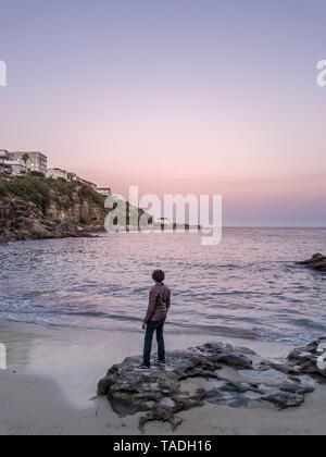 Un modello maschile in un rivestimento permanente sulla roccia presso la riva del mare godendo il bellissimo tramonto Foto Stock
