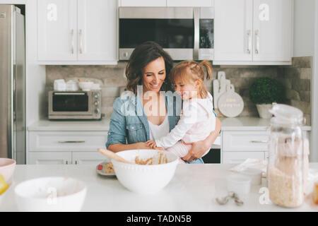 Madre e figlia facendo una torta insieme Foto Stock
