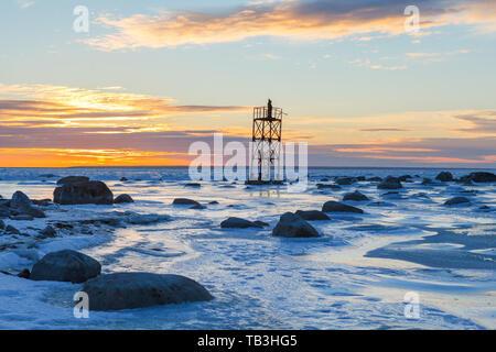 Monaco sul militare abbandonato guarda la torre, arancione tramonto sul mare ghiacciato coast Foto Stock