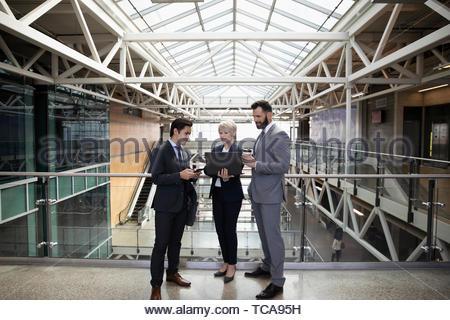 La gente di affari di parlare, utilizzando laptop su office atrium balcone Foto Stock