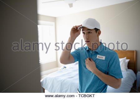 Ragazzo adolescente ottenere pronto per lavoro, mettendo in uniforme e tag name Foto Stock