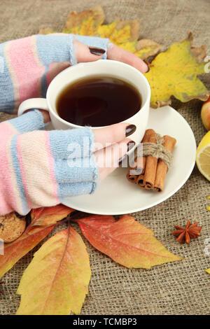 Mani tazza di una bevanda calda e foglie di autunno, su sfondo di tela Foto Stock