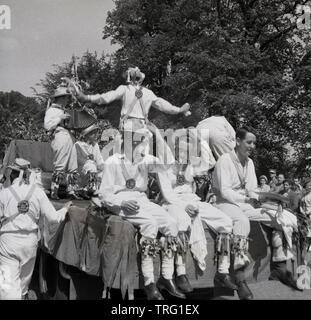 Degli anni Cinquanta, storico in una calda giornata estiva, un gruppo dei maschi di morris ballerini giocando su un galleggiante di carnevale, con tre di loro di prendere una pausa dal ballo di godere di un periodo di riposo e di una sigaretta, Inghilterra, Regno Unito. Morris Dance è un tradizionale English Folk Dance e una parte importante dell'estate fetes e carnevali, Foto Stock
