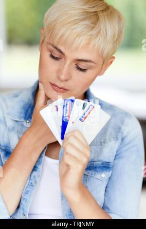 Donna che guarda interessato tenendo le carte di credito Foto Stock
