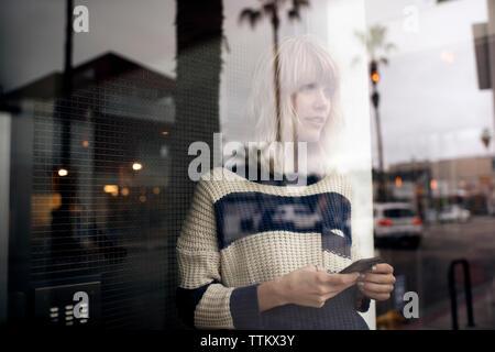 Premurosa donna giovane azienda smart phone visto attraverso la parete in vetro Foto Stock