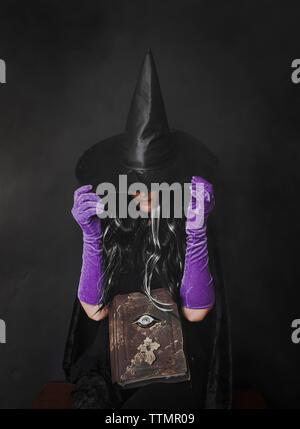 Donna vestito in costume strega seduta su sfondo nero durante il periodo di Halloween Foto Stock