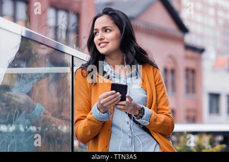 Giovane donna texting sul marciapiede Foto Stock