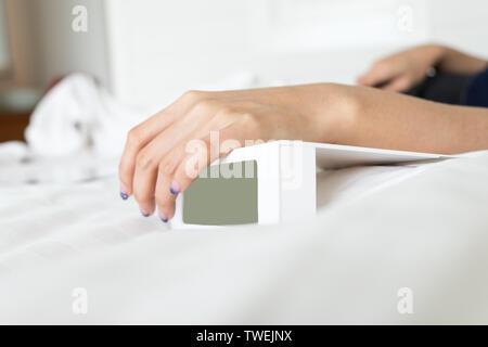 Donna mano su bianco sveglia digitale in camera al mattino Foto Stock