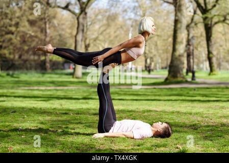 Coppia giovane fare yoga acrobazie in un parco urbano Foto Stock