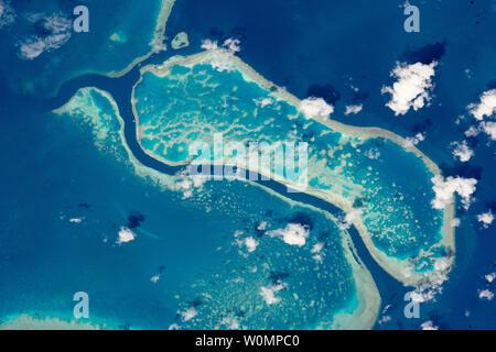 Un astronauta a bordo della Stazione Spaziale Internazionale catturato una vista di questi tre scogli in Australia la Grande Barriera Corallina su ottobre 12, 2015. L'area di foto si estende per circa dieci miglia di 1.700 miglia sistema di barriera corallina. Le scogliere sono facili da individuare dalla spazio poiché l'iridato blues di lagune forte contrasto con il blu scuro delle acque profonde. La Grande Barriera Corallina è il più grande sistema corallino sulla terra, con più di 3 mila barriere separate e formazioni coralline. È anche uno dei più complessi ecosistemi naturali, con 600 tipi di coralli e migliaia di specie animali da minuscoli planktons balene. Foto Stock