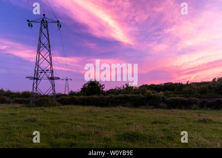 Potenza e tralicci linee che conducono fuori nella distanza con un tramonto incrediable overhead, nessuno nell'immagine Foto Stock