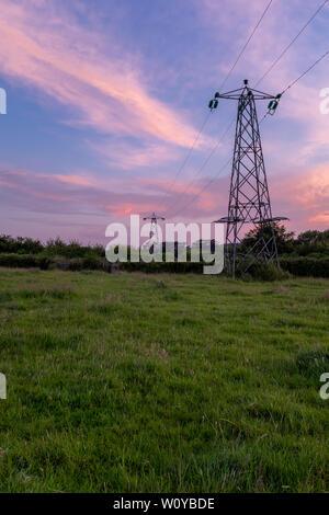 Una vista verticale di linee di potenza e tralicci che conducono fuori nella distanza con un tramonto incrediable overhead. Nessuno nell'immagine Foto Stock