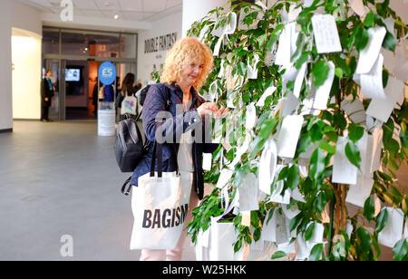 Liverpool Merseyside Regno Unito - una donna perni un messaggio a immaginare la pace mostra di Yoko Ono e John Lennon presso il Museo di Liverpool fotografia scattata Foto Stock