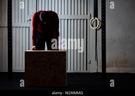 Stanco uomo sportivo dopo box jumping esercizio appoggiata sulla scatola. Immagine scura. Foto Stock