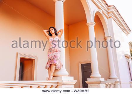 Donna in abiti floreali appoggiata contro la colonna Foto Stock